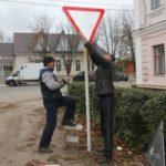 мужчины меняют дорожный знак